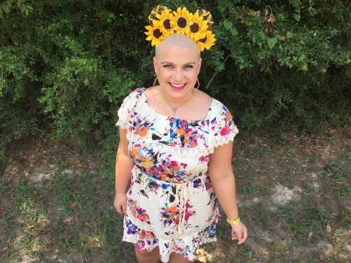 Nicole wearing sunflower ears in a white and flowery dress standing in front of green trees with a large smile on her face as she just lost her fair from chemotherapy.
