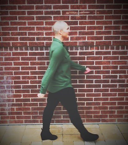 Nicole walking to the right slightly blurred out smiling in a green shirt in front a brick wall