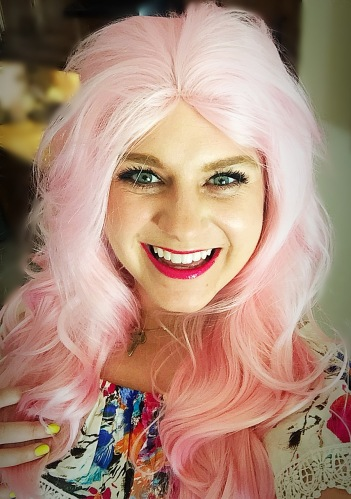close up of Nicole in her pink wig with pink lipstick smiling.