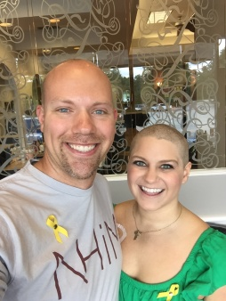 Wes and Nicole standing smiling after they have their heads shaved prior to Nicole losing her hair through chemo.
