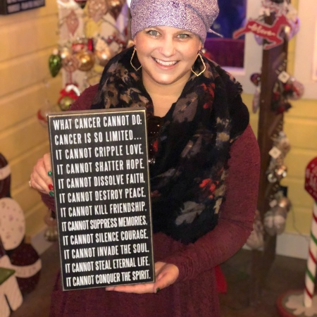 "Nicole holding a sign stating ""what cancer cannot do"""