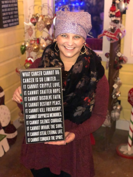 """Nicole holding a sign stating """"what cancer cannot do"""""""
