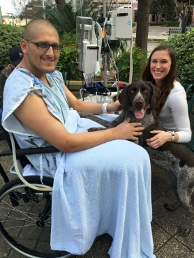 Issac and Shelby outside with a puppy as Issac is in a hospital gown with his IV pole next to him having chemo adminstered.