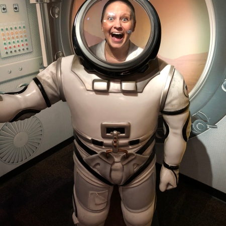 Nicole standing with her mouth open in a NASA spacesuit