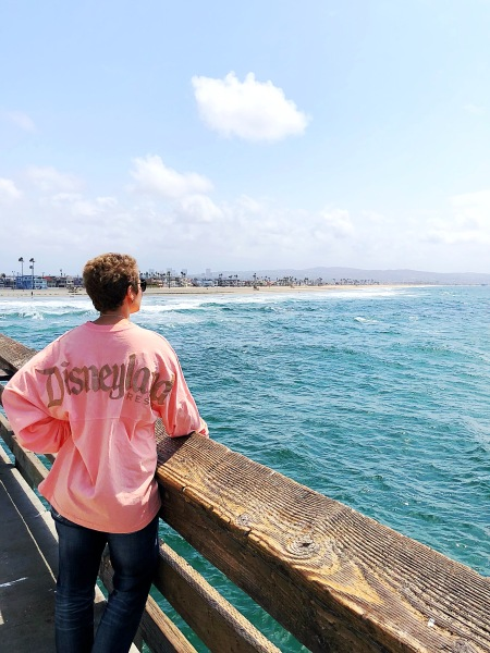 Nicole looking out at the ocean off of a pier with her back facing the camera in a pink Disneyland shirt