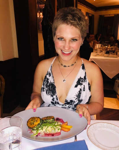 Nicole holding up her meal of swordfish at Club 33 in Disneyland