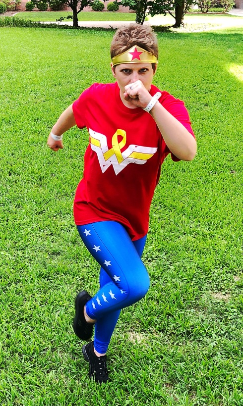 Nicole running showing off her Wonder Woman shirt with the cancer ribbon