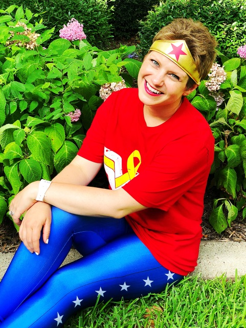 Nicole smiling and sitting by a flower bush in her Wonder Woman outfit