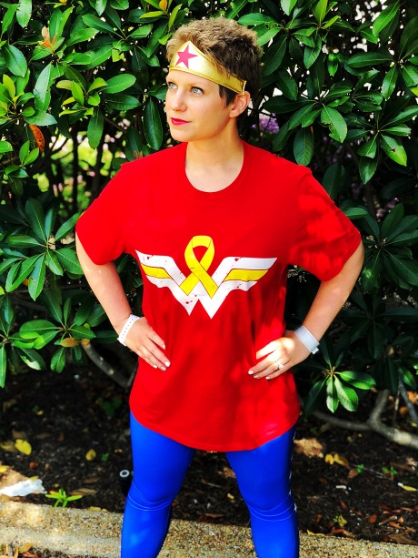 "Nicole standing in a Wonder Woman costume that has a yellow cancer ribbon in the white space of the ""W"""