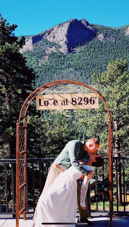 "Wes dipping Nicole and kissing her under a sign that says ""Love at 8296 feet"" with the mountains in the background."