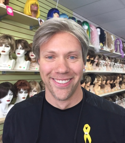 Wes trying on a gray wig in a wig store to make me laugh while he wears a yellow ribbon on his shirt supporting sarcoma awareness.