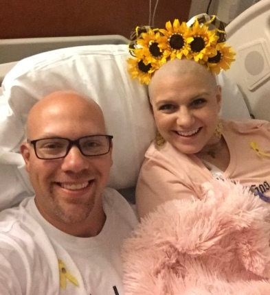 Wes lying in the hospital bed with Nicole while she has chemo adminstered.
