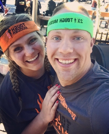 Wes and Nicole smiling together wearing their tough mudder headbands and shirts.