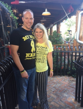 Wes and Nicole wearing sarcoma awareness shirts standing on the patio of a restaurant.