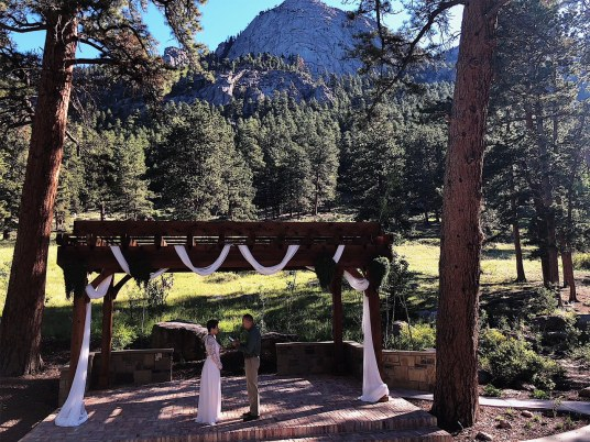 At the Della Terra Mountain Chateau in Estes Park renewing our vows together with the mountains in the background as we stand under an awning.