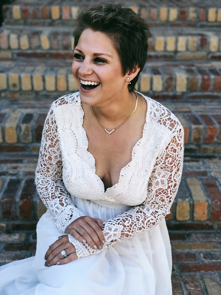 Nicole sitting on a staircase laughing in her white gown for her vow renewal.