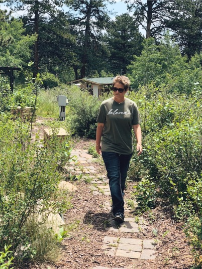 "Nicole walking down a path in the mountains with a shirt on that says ""Beloved"""