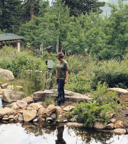Nicole looking down at the water in a pond outside in the mountains.