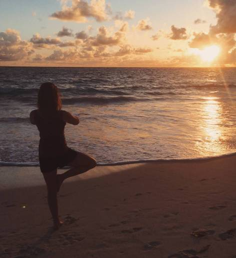 Standing in a Yoga Pose on the beach looking at the sunset