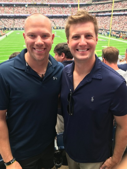 Michael and Wes smiling with a football field in the background at a Houston Texans football game.