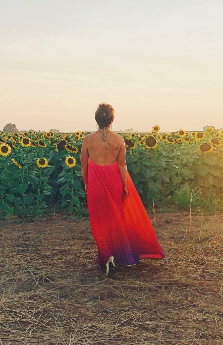 Nicole walking off into the distance towards sunflowers.