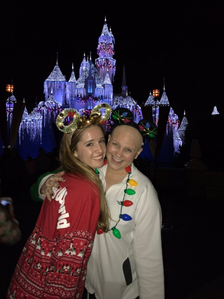 Jenna and Nicole standing in front of the castle all lit up for in purple crystals with our mouse ears on smiling at Disneyland.