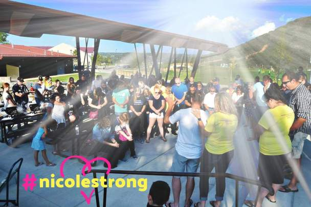 A large gathering of people praying outside with rays on sunshine beaming down at a fundraiser for Wes and me during treatment.