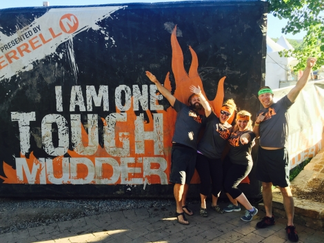 "Jeffrey, Kelsey, Nicole, and Wes posing in front of the ""I AM ONE TOUGH MUDDER"" banner before the race."