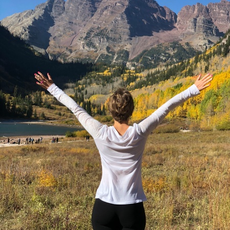 Nicole's back facing the camera with her hards up as she looks at the Maroon Bells in Aspen