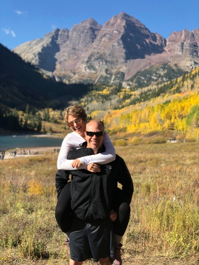 Nicole on Wes' back with the Maroon Bells in the background