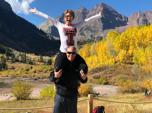 Nicole on Wes' shoulders smiling with the Maroon Bells in the background.