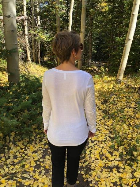 Nicole's back as she is in the midst of many aspen trees