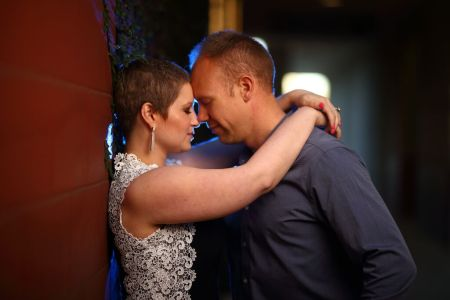 Nicole and Wes up against a wall with heads tenderly pressed against one another with eyes closed.