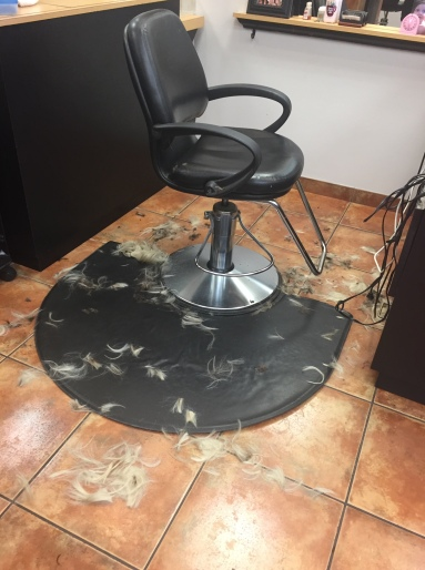 An empty salon chair pictured with Nicole's hair on the floor