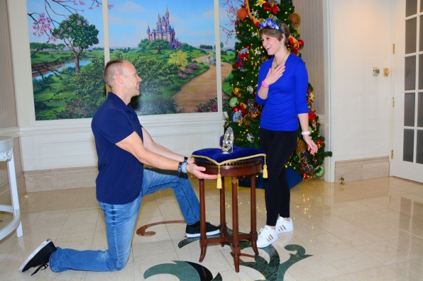 Wes kneeling down presenting Cinderella's glass slipper to her with a castle and tree backdrop.