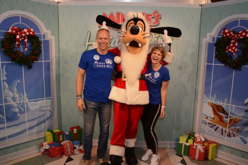 Nicole and Wes taking a fun photo with Goofy dressed up as Santa. Nicole is laughing as Goofy is holding his ears up!