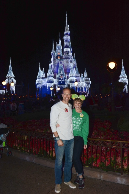 """Wes and Nicole standing in front of Cinderella's Castle at Magic Kingdom as it is """"frozen"""" with the holiday lights. Nicole's shirt says """"faith, trust, and pixie dust"""" on it."""