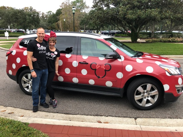 """Wes and Nicole standing in front of the """"Minnie Van"""" red and white polka dot Lyft vehicle at Disney World"""