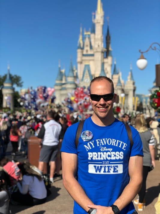 "Wes wearing a shirt in front of Cinderella's Castle at the Magic Kingdom that says ""My favorite Disney Princess is my wife."""