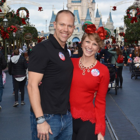 Wes and Nicole standing in front of Cinderella's Castle at Magic Kingdom wearing their Christmas attire.