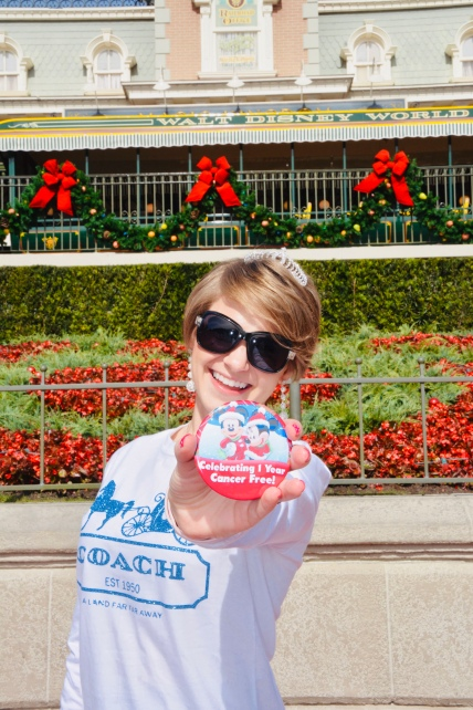 Nicole holding up her one year cancer free button with the Magic Kingdom entrance in the background.