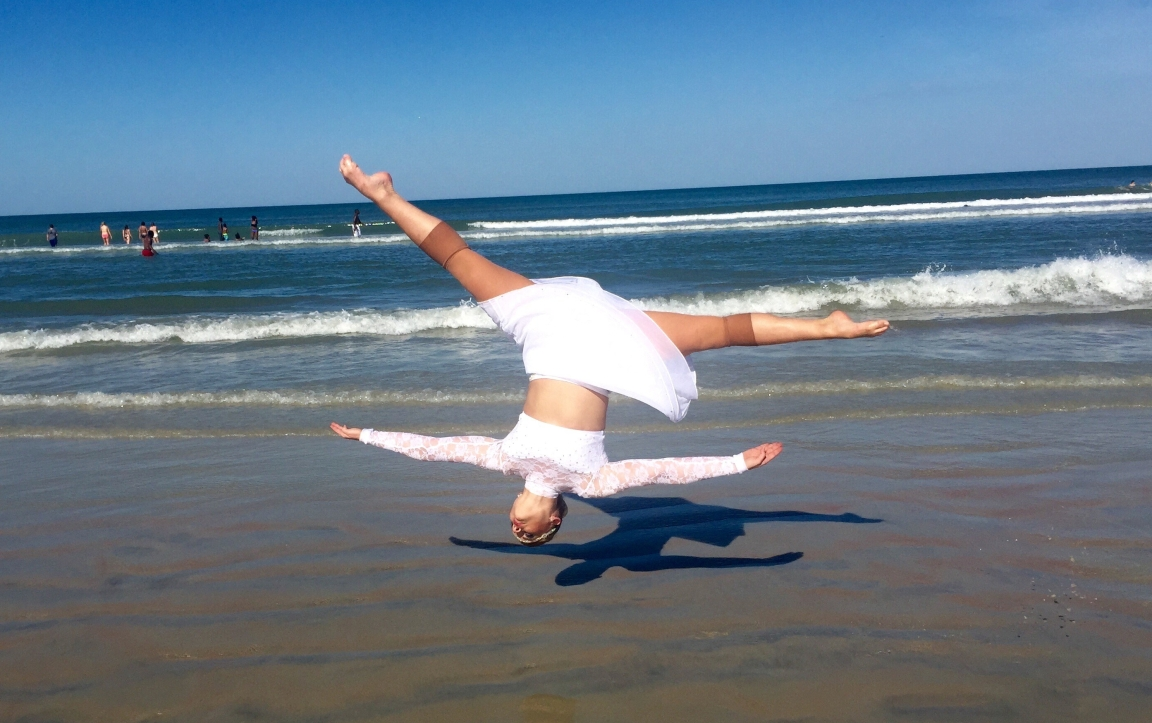 Brooke doing an aerial cartwheel on the beach dressed in white