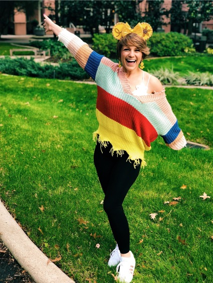 Nicole standing outside with her arms spread wide celebrating cancer free scan results