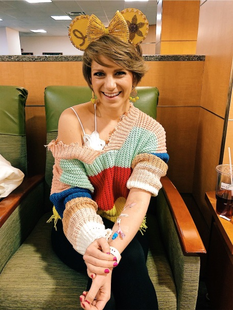 Nicole sitting showing her IV in her arm waiting for her CT Scan