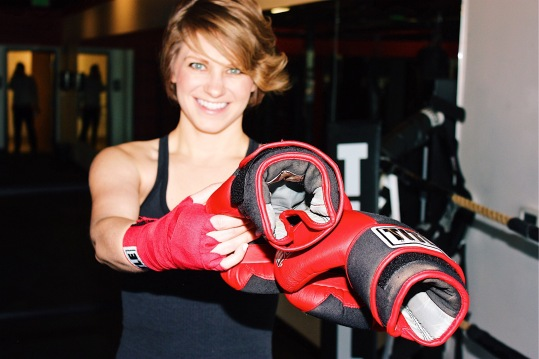 Nicole handing off her boxing gloves to the next fighter that will enter the ring.