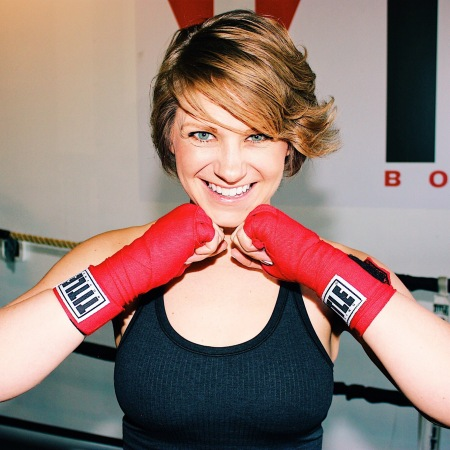 Nicole smiling with her boxing hand wraps pressed up against her face.