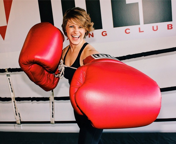 Nicole wearing giant boxing gloves laughing at the camera.