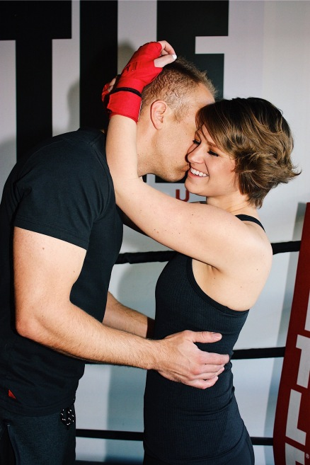 Wes kissing Nicole with her hands wrapped in boxing hand wraps around his head.