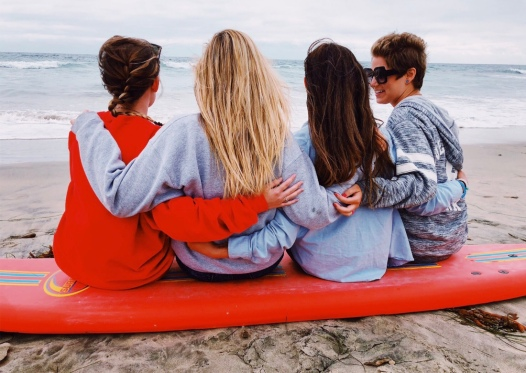 Brooke, Maddie, Sabrina, and Nicole sitting on a surfboard chatting by the ocean in California.