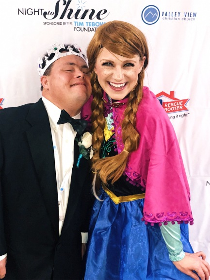 Nicole dressed up as Anna from Frozen volunteering at Night to Shine with one of the honored guests.